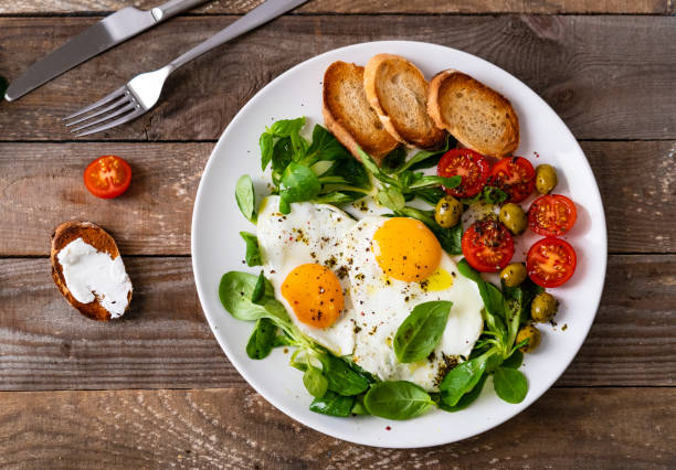 Breakfast - toasts, fried egg and vegetables stock photo