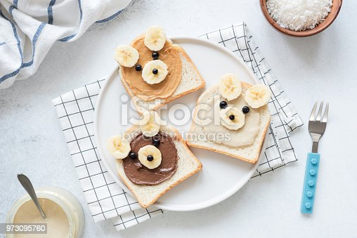 istock Breakfast toasts with nut butter and banana with cute funny animal face. Kids food 973095760