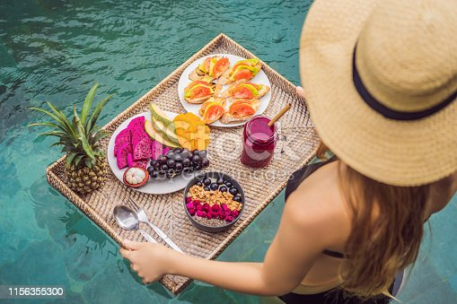 Breakfast tray in swimming pool, floating breakfast in luxury hotel. Girl relaxing in the pool drinking smoothies and eating fruit plate, smoothie bowl by the hotel pool. Exotic summer diet. Tropical beach lifestyle. Bali Trend.
