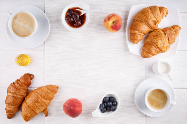 Breakfast - two cups of coffee, croissants, jam, honey and fruits on white table.  Top view. Copy space. stock photo