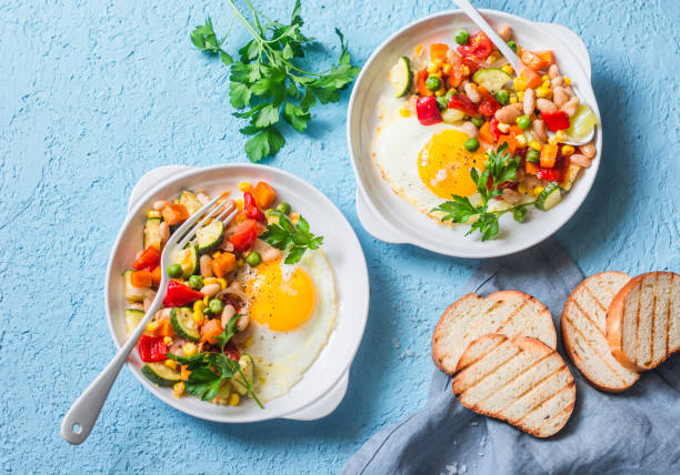 Breakfast vegetable hash with fried eggs on a blue background, top view. Healthy food concept stock photo