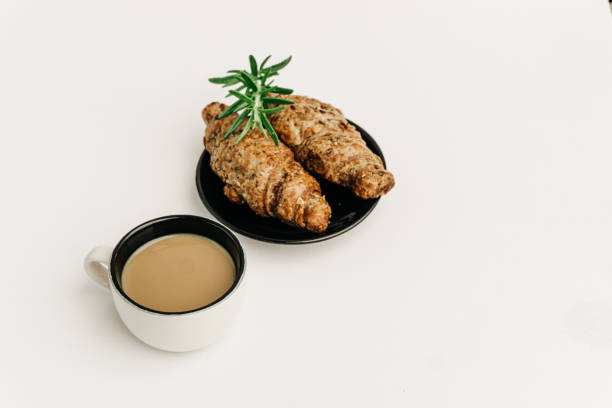 Breakfast with a coffee and organic seed croissants isolated on white. Minimalist and black and white image. stock photo