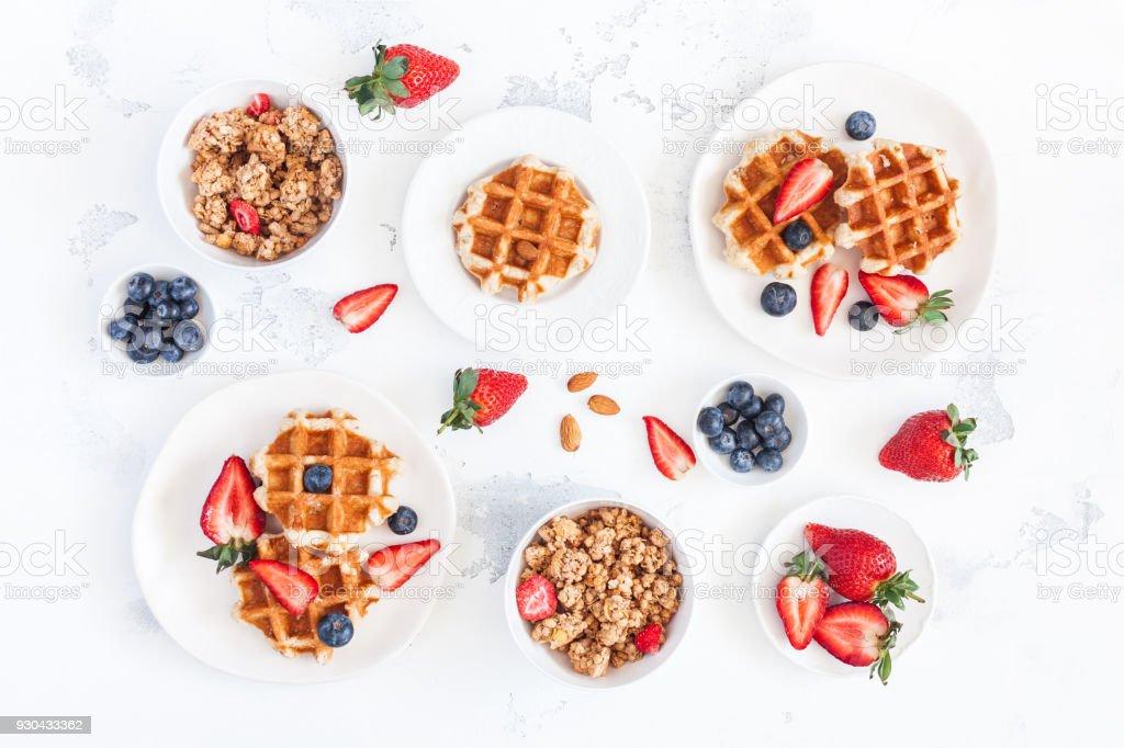 Breakfast with belgian waffles, muesli, fruits. Flat lay, top view stock photo