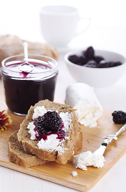 Breakfast with bread, blackberry jam and fresh goat cheese stock photo