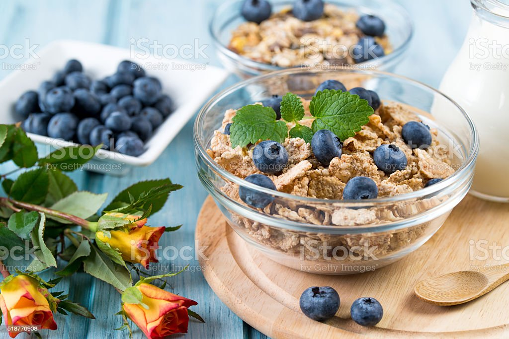 Breakfast with cereal, blueberry, milk and rose flowers stock photo