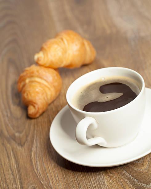 Frühstück mit Kaffee und croissants in einem Korb auf dem Tisch – Foto