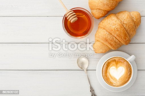 istock Breakfast with coffee and croissants on white rustic table 862605102