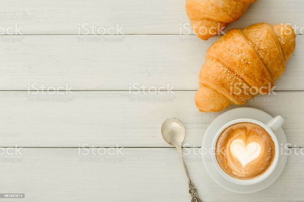 Breakfast with coffee and croissants on white rustic table stock photo