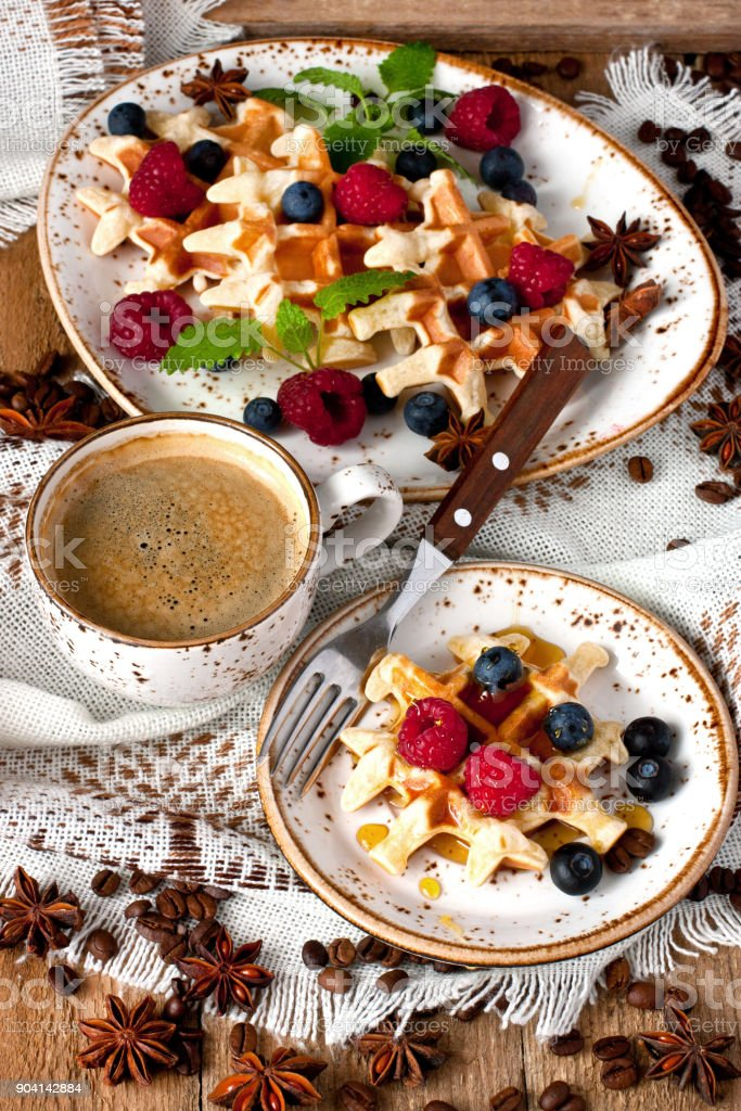 Waffles with berries on ceramic plate and coffee mug on wooden table