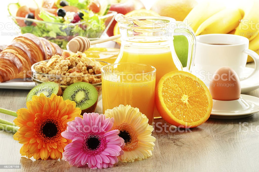 Breakfast with coffee, juice, croissant, salad, muesli and egg stock photo