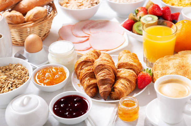 Breakfast with croissants, coffee, juice, meat, jam, cereals and fresh fruits stock photo