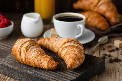 Breakfast with croissants, coffee, orange juice and berries on wooden table. Closeup view, selective focus