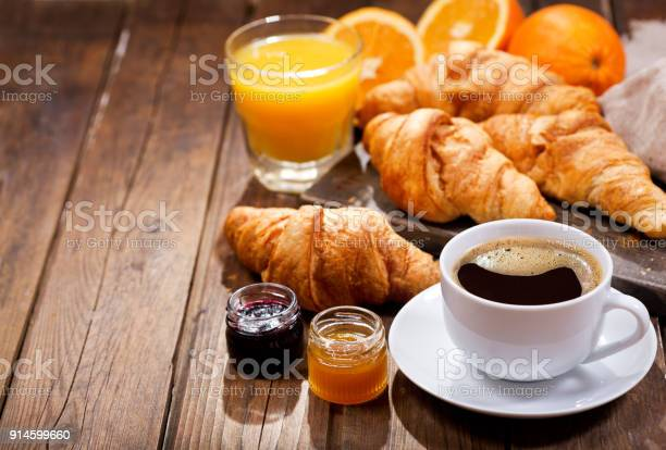 breakfast with cup of coffee, croissants, orange juice and fruit jam on wooden table