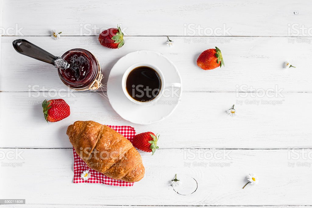 breakfast with cup of coffee, croissant, jam and strawberries stock photo