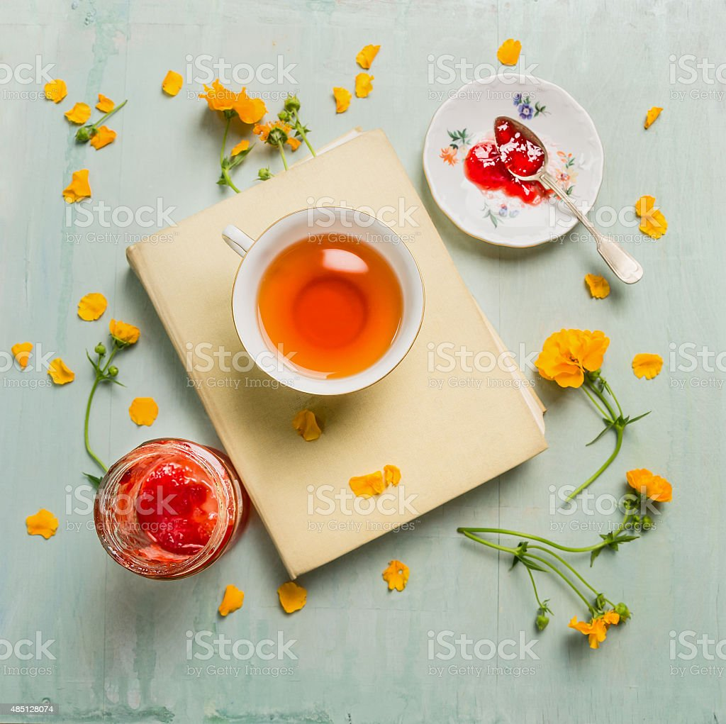 Breakfast with cup of tea, book, jam and flowers stock photo