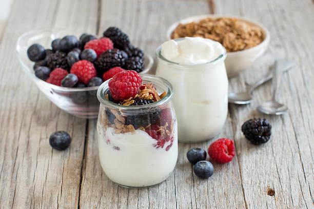 le petit déjeuner grec avec des yaourts, du muesli et fruits des bois - yaourt photos et images de collection