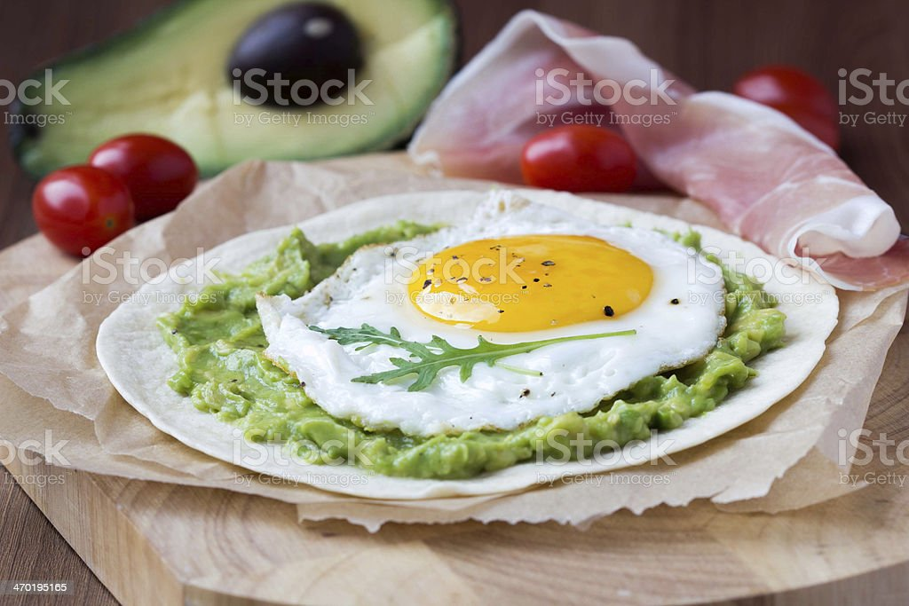 Breakfast with fried egg, sauce of avocado on grilled flour stock photo