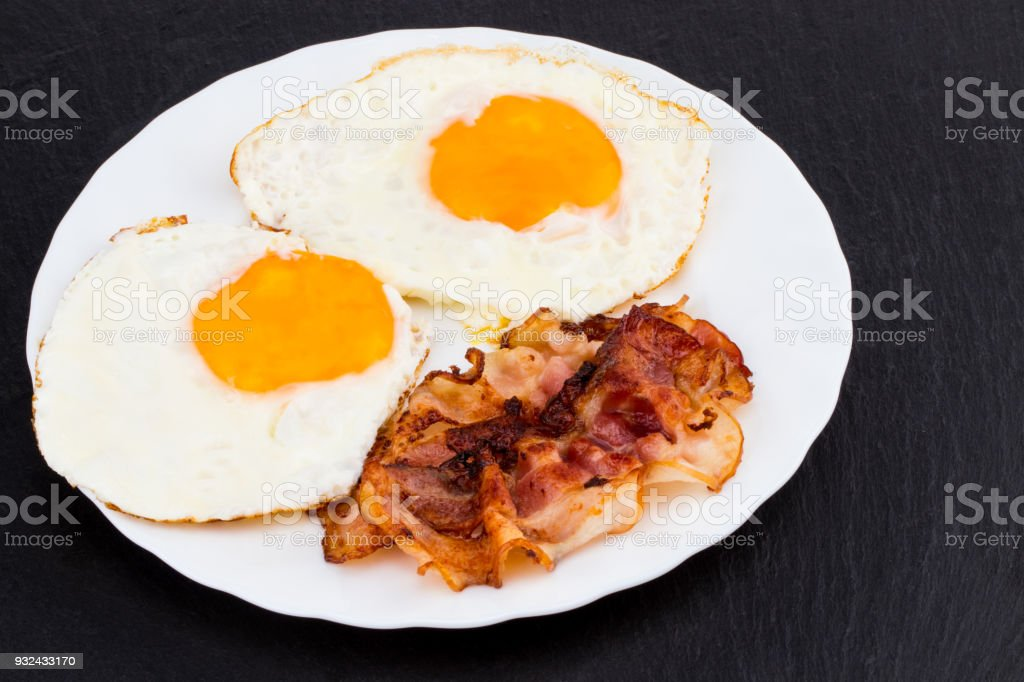 Breakfast with fried eggs and bacon on dark stone background stock photo