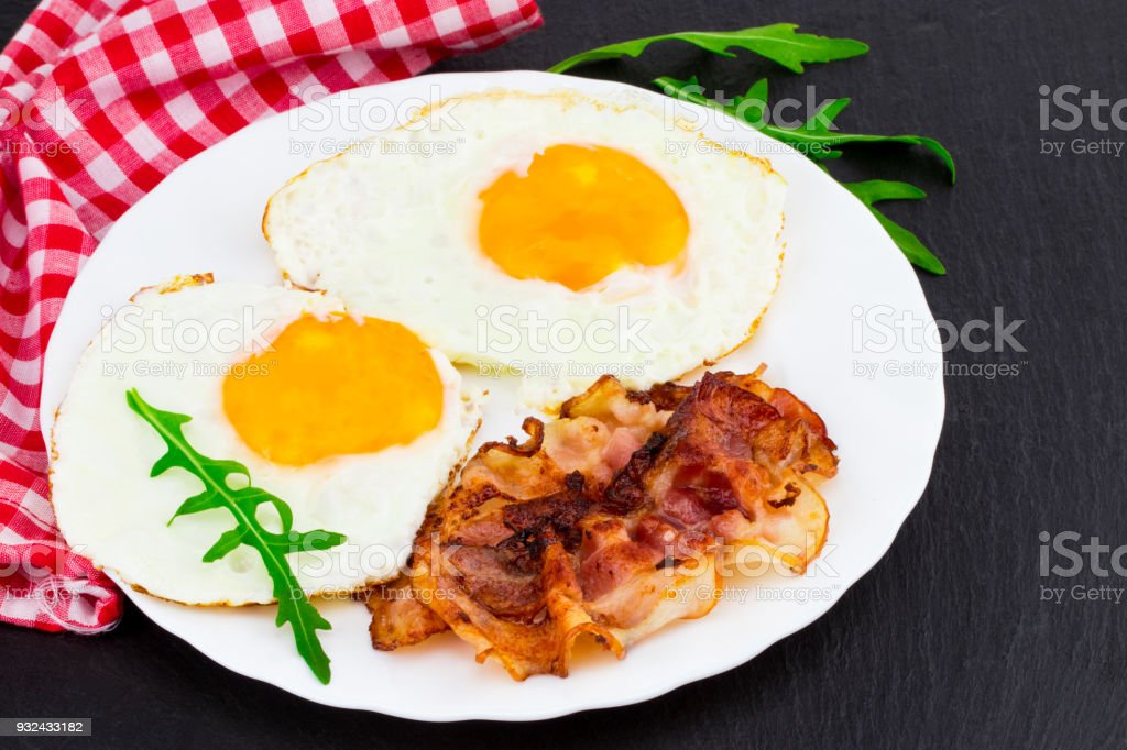 Breakfast with fried eggs, bacon and rucola salad on dark stone background stock photo
