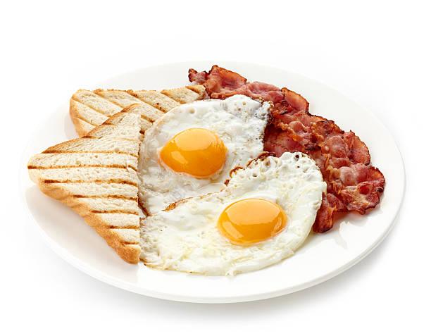 desayuno con huevos fritos, tocino y toasts - desayuno fotografías e imágenes de stock