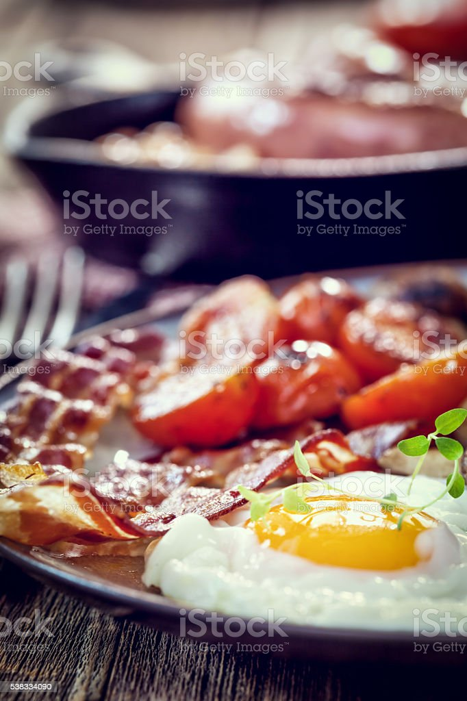 Breakfast with fried eggs, bacon, beans and cherry tomatoes stock photo