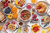 istock Breakfast with granola, croissant, fresh waffles, fruits and berries 1142264910