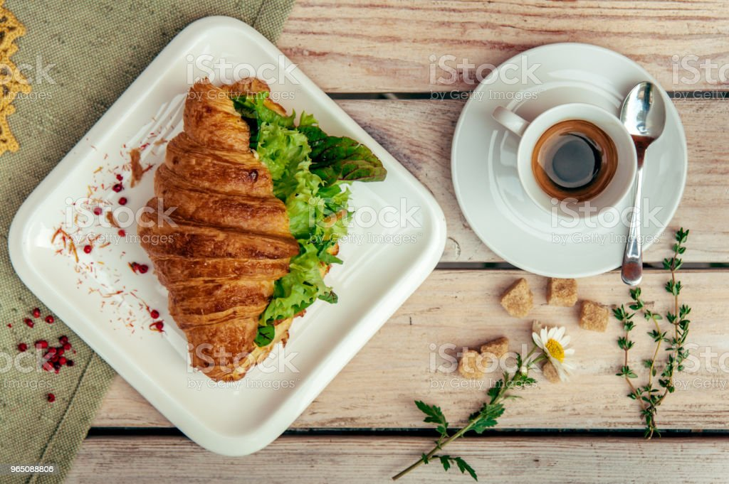 breakfast with green croissant, black coffee decorated with chamomile and brown shugar on wooden table. zbiór zdjęć royalty-free