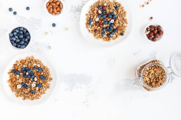 breakfast with muesli, blueberry, nuts. flat lay, top view - oats food stock photos and pictures