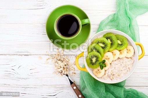 istock Breakfast with oatmeal porridge and coffee cup. Oatmeal with kiwi and banana. Healthy breakfast concept. Top view 692530540