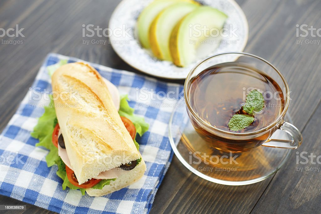 Breakfast with sandwich, tea and melon royalty-free stock photo