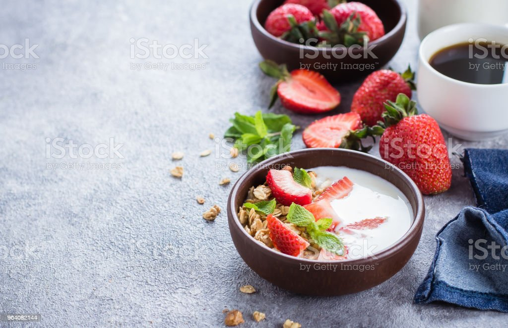 Breakfast with yogurt, granola of muesli and strawberries on gray concrete table background. Healthy Vegan Clean Diet Food Concept. Copy space - Royalty-free Antioxidant Stock Photo