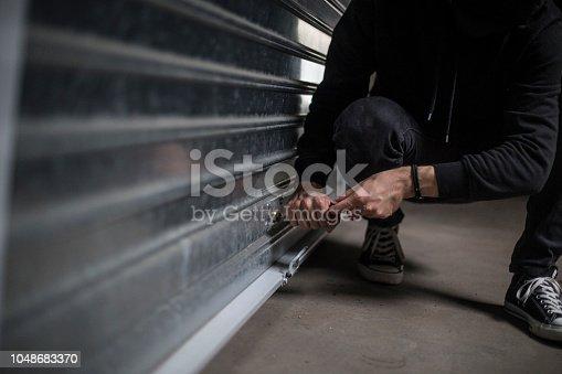 Unrecognizable Caucasian male burglar trying to rob a garage.