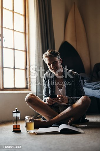 Shot of a handsome young man taking a break from reading to send a text message while sitting on the floor at home