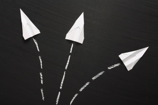 Three paper airplanes break formation and take flight across a blackboard surface