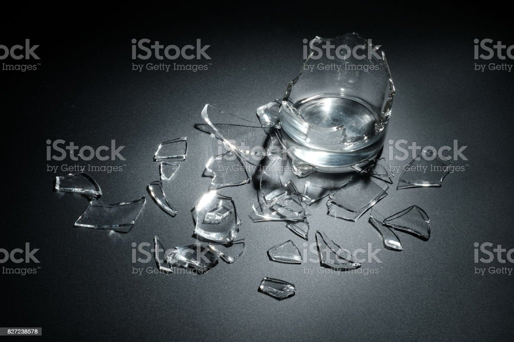 A breaking glass of water on the black background stock photo
