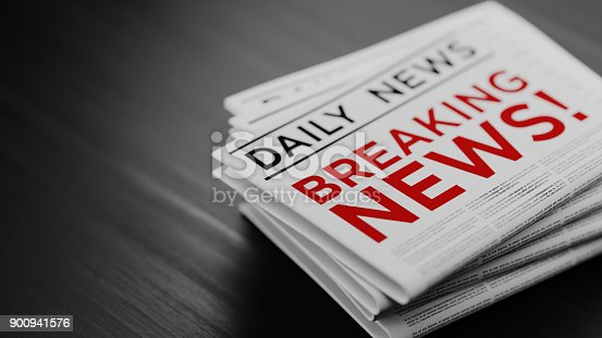 Breaking news concept. Newspaper pile is sitting on black wood surface. Horizontal composition with selective focus and copy space.