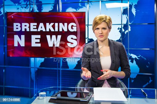 Woman sitting in news studio with breaking news sign behind her. Ready to go live.