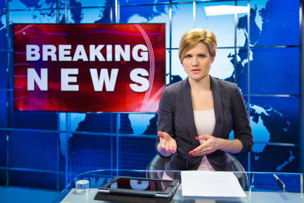 Breaking news female anchor Woman sitting in news studio with breaking news sign behind her. Ready to go live. anchor stock pictures, royalty-free photos & images