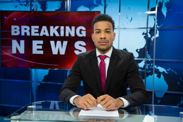 Breaking news male anchor Man sitting in news studio with breaking news sign behind her. Ready to go live. Afro-american descent. anchor stock pictures, royalty-free photos & images