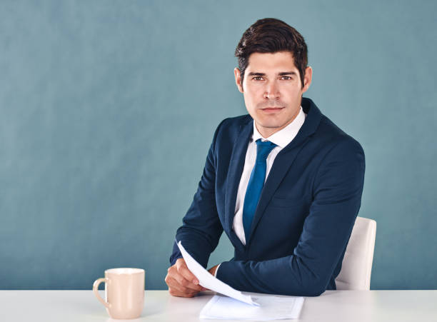 Breaking news Cropped portrait of a handsome young male newscaster sitting in the newsroom anchor stock pictures, royalty-free photos & images
