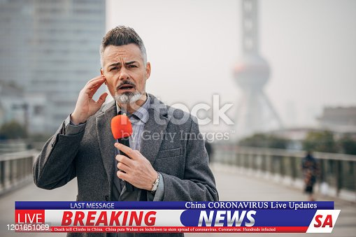 One man, handsome breaking news reporter, going live in television program, reporting on coronavirus from Shanghai.