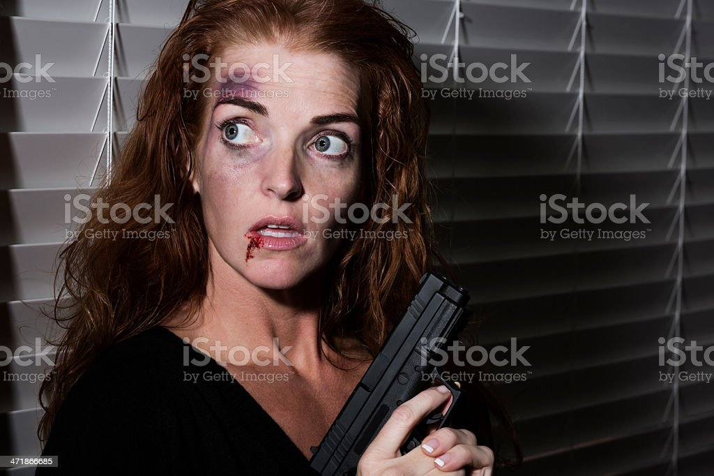 Breaking point: Abused woman protecting herself with a gun royalty-free stock photo