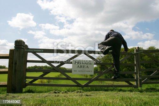 A man climbing over a gate into a 'Private area'
