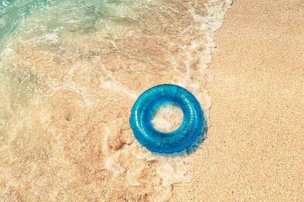 breaking wave and rubber ring on pedn vounder beach, cornwall - rubber ring stock pictures, royalty-free photos & images