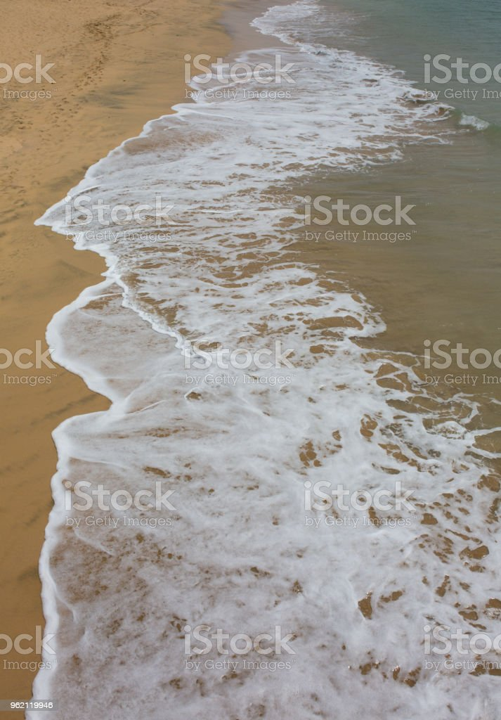 Breaking wave on golden sand beach directly shot from above stock photo