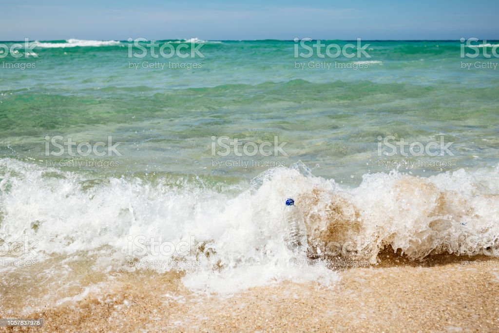 Breaking wave with plastic bottle, motion blur. stock photo