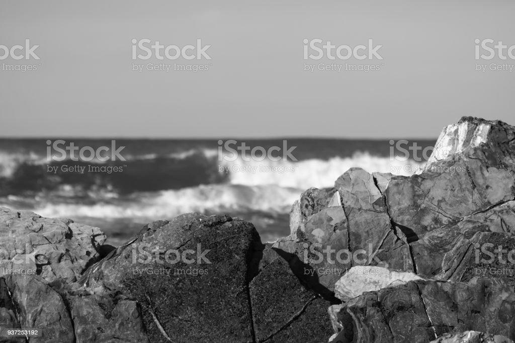 breaking waves against rocks in black and white