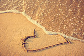 Heart drawn on the beach sand being washed away by a wave. Sand tone. Love affair, summer love or breakup and divorce concept. Ephemeral romantic love. Not true love. End of relationship.