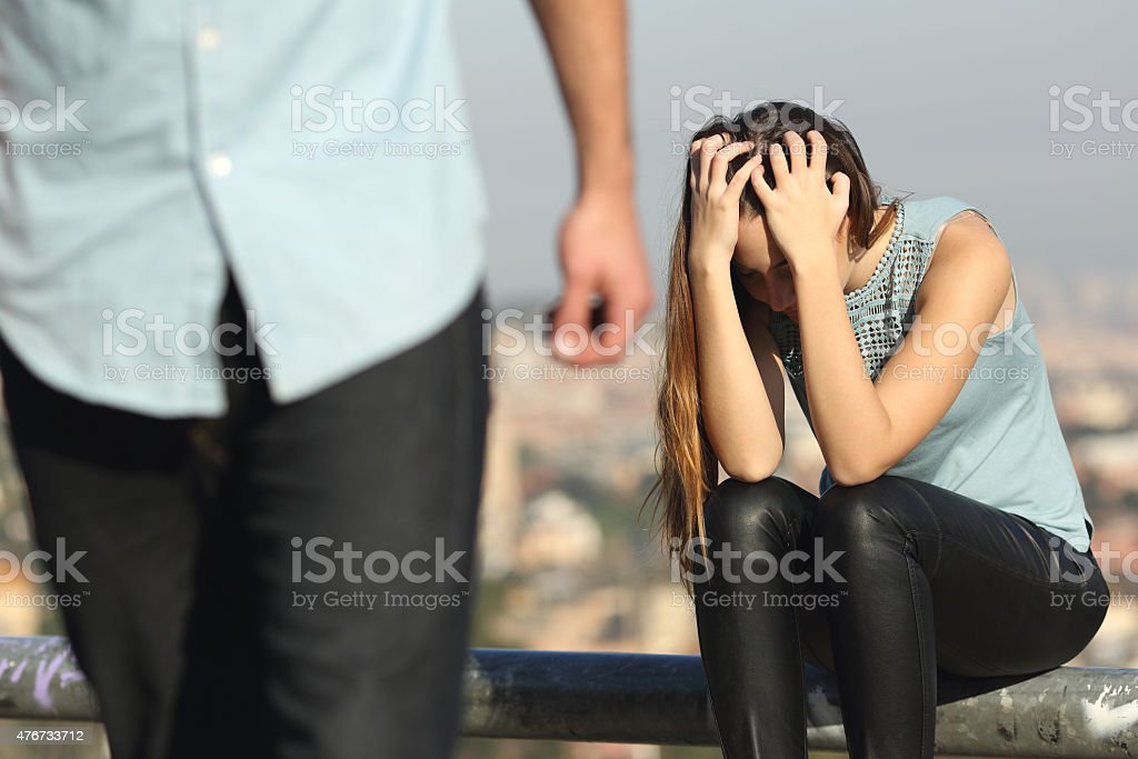 Breakup of a couple with bad guy and sad girlfriend stock photo