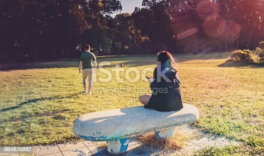 istock Breakup of a couple with guy leaving and sad girlfriend staying on the bench 664826882